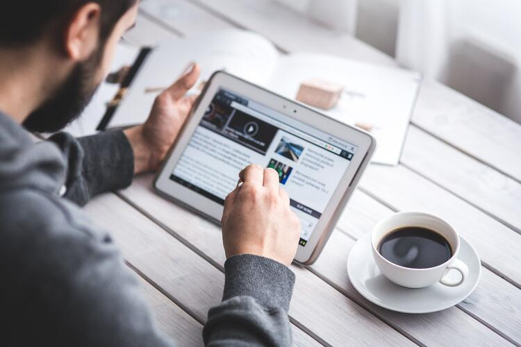 man scrolling through article with stylus on tablet